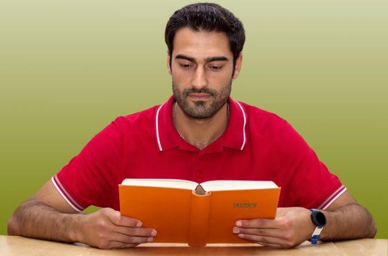 """Ein Mann liest ein Buch mit der Aufschrift """"Deutsch""""."""